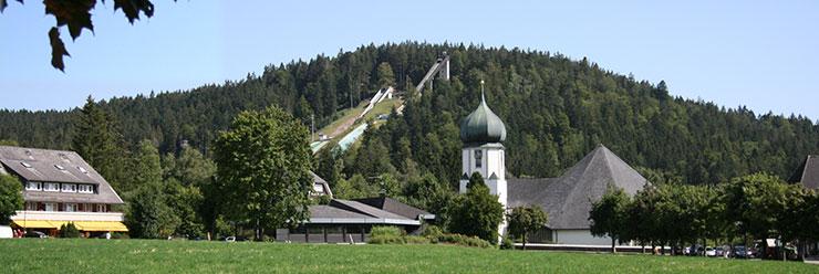 Skisprungzentrum Hinterzarten mit Zwiebelturmkirche im Vordergrund